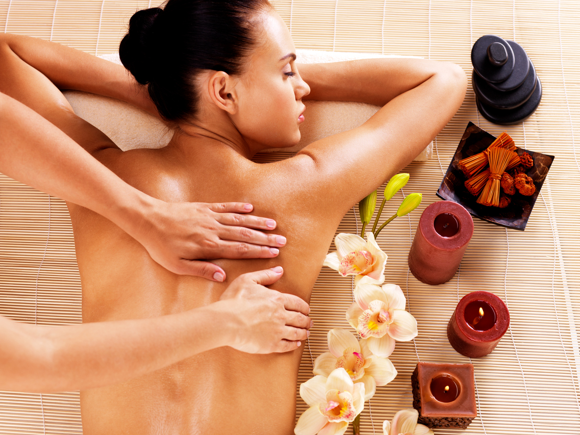 Adult woman in spa salon having body massage.